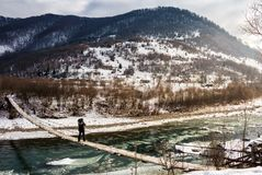 Cold flow of river in snowy mountains. Ice and snow on the rocky shore. gorgeous winter scenery in rural area on a cloudy day Royalty Free Stock Images