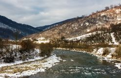 Cold flow of river in snowy mountains. Ice and snow on the rocky shore. gorgeous winter scenery in rural area on a cloudy day royalty free stock photo