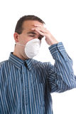 Cold and Flu. A young man with a respiratory infection is wearing a mask to protect others and is suffering from a headache, isolated against a white background Royalty Free Stock Images