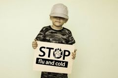 Cold and flu in children`s feet concept. Photo with text for your design. the boy is holding a wooden board in his hands Stock Images
