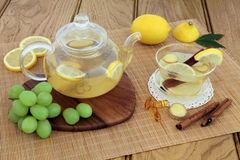 Cold and Flu Remedy Drink. Cold and flu remedy with hot lemon, honey and ginger drink in glass tea cup and teapot, with grapes, spices and  multi vitamin tablets Stock Images