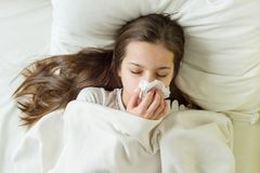 Sick girl on bed sneezing in handkerchief in bedroom. Cold flu season, runny nose. Sick girl on bed sneezing in handkerchief in bedroom Royalty Free Stock Image