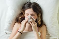 Cold flu season, runny nose. Sick girl on bed sneezing in handkerchief in bedroom.  Royalty Free Stock Images