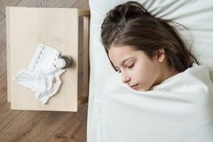 Cold flu season. Sick girl child in bed, near bed medication napkin.  royalty free stock photos