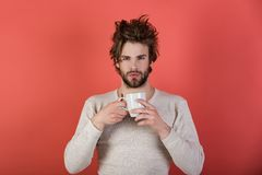 Cold and flu, single. Man with disheveled hair drink mulled wine. Insomnia, refreshment and energy. Sleepy guy with tea cup on red background. Morning with royalty free stock photos