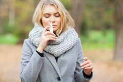 Cold and flu. Young sick woman uses a nose spray at street outside.  royalty free stock images