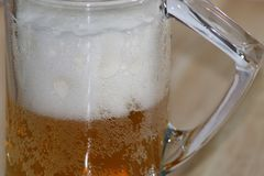 Cold foam beer into glass cup stock images