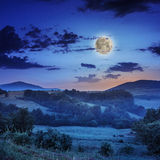 Cold fog on hot sunrise in mountains with moon Royalty Free Stock Images