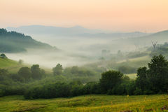 Cold fog on hot sunrise in mountains Stock Image