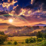 Cold fog on hot sunrise in mountains with rainbow Royalty Free Stock Photography