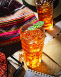 Cold fragrant tea in a glass on the original napkin, mint leaves Royalty Free Stock Images