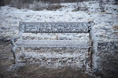 Cold winter photography image of outdoor bench or seat covered in wind swept frozen water and ice with snow background. Cold freezing winter weather image with a Stock Photography