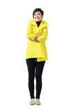 Cold freezing woman wearing yellow coat with crossed arms looking up Royalty Free Stock Photos