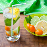 Cold fresh drink with lemon, lime, kumquat and mint. Stock Photography