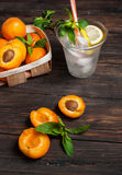 Cold fresh lemonade and apricots on wood background Stock Photo