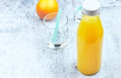 Cold fresh orange juice in a bottle on light concrete. horizontal view, copy space. Citrus refreshing detox drink stock images