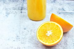 Cold fresh orange juice in a bottle on light concrete. horizontal view, copy space. Citrus refreshing detox drink royalty free stock photos