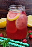 Cold fresh raspberry lemonade in a glass jar on table. Cold fresh raspberry lemonade in a glass jar on wooden table Stock Photo