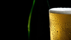 The cold frothy beer in a glass on a black background. Beer in a glass on a black background Stock Image