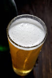 The cold frothy beer in a glass on a black background. Beer in a glass on a black background Stock Photo