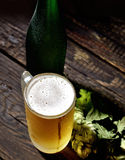 Cold frothy beer in a glass bottle and hops on a dark wooden background. Cold frothy beer in a glass bottle and hops Royalty Free Stock Photography