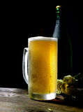 Cold frothy beer in glass, bottle and hops on a wooden background. Cold frothy beer in glass, bottle and hops Stock Image