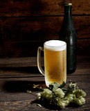 Cold frothy beer in glass, bottle and hops on a wooden background Stock Photo