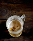 Cold frothy beer in a glass on a dark wooden background Stock Images