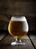 Cold frothy beer in a glass on a dark wooden background Royalty Free Stock Images