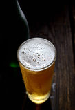 He cold frothy beer in a glass  on a dark wooden background. Beer in a glass on a wooden background Stock Photos