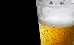 He cold frothy beer in a glass  on a dark wooden background. Beer in a glass on a wooden background Royalty Free Stock Photos