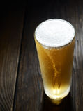 He cold frothy beer in a glass  on a dark wooden background. Beer in a glass on a wooden background Royalty Free Stock Image