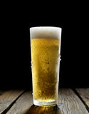 He cold frothy beer in a glass  on a dark wooden background Royalty Free Stock Photography