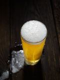 The cold frothy beer in a glass  on a dark wooden  background. Beer in a glass on a wooden background Stock Photography
