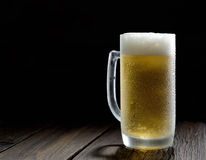 Cold frothy beer in a glass  on a dark wooden background. Cold frothy beer in a glass  and hops Royalty Free Stock Photo