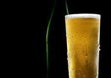 The cold frothy beer in a glass and a green bottle on a dark  background. Beer in glass and bottle on a black background Royalty Free Stock Photography