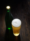 The cold frothy beer in a glass and a green bottle on a dark wooden background Stock Images