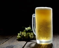 Cold frothy beer in a glass and hop on a gray wooden background. Cold frothy beer in glass and hops Royalty Free Stock Photography