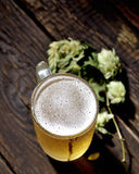 Cold frothy beer in glass and hops on a wooden background Stock Photography