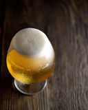 Cold frothy beer in a glass of original color on a on a wooden  background Stock Photography