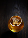Cold frothy beer in a glass of original color on a on a wooden  background Royalty Free Stock Photo