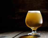 Cold frothy beer in a glass of original color on a on a wooden  background Royalty Free Stock Images
