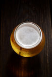 Cold frothy beer in a glass of original color on a on a wooden  background Stock Photo