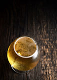 Cold frothy beer in a glass of original color on a on a wooden  background Royalty Free Stock Photos