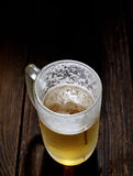 Cold frothy beer in a glass on a wooden background Stock Photos