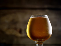 Cold frothy beer in a glass on a wooden background Stock Photography
