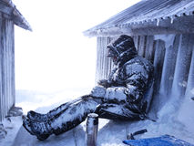 Cold. A frozen man sitting between two old wooden house in really cold temperatures Stock Photography
