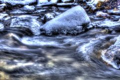 Cold frozen mountain river stream in the cold winter forest in the deep arctic circle wilderness Stock Image