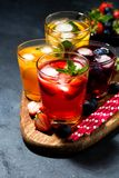 Cold fruit and berry beverages in assortment on dark background. Vertical top view royalty free stock image