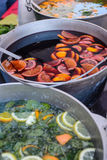 Cold fruit drinks on the outdoor village fair. Icy drinks from the pieces of fruit and mint leaves in a saucepan on a village fair royalty free stock photo